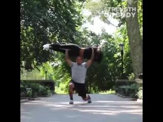 Парень тренируется с девушкой в парке