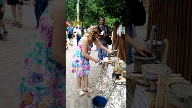 Красивая девушка шлифует камни на древнем станке. Фестиваль.