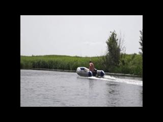 Какой-то мужик проплывает на моторной лодке мимо обычной деревянной нашей по реке Сейм близ село Кувшинное
